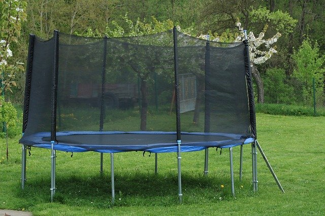 trampolína s ochrannou sítí na zahradě.jpg
